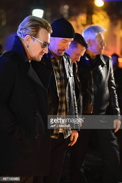 Bono and band members of U2 pay their respects and place flowers on the pavement near the scene of yesterday's Bataclan Theatre terrorist attack on...