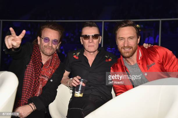 Bono and Larry Mullen Jr of the band U2 pose with David Guetta during the MTV EMAs 2017 held at The SSE Arena Wembley on November 12 2017 in London...