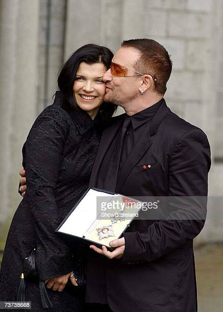 Bono birth name Paul Hewson poses with his wife Ali Hewson after receiving a Knighthood from Ambassador David Reddaway awarded to him by Her Majesty...