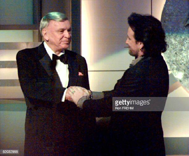Bono, lead singer of the group U2 , shakes hands with singer Frank Sinatra after Sinatra was honored with a Lifetime Achievement Award at the 36th...