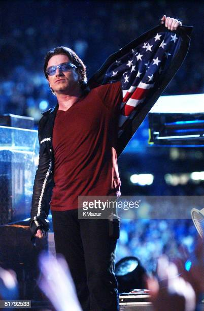 Bono lead singer of U2 displays American flag lining in his jacket after singing 'Where The Streets Have No Name' during the halftime show of Super...
