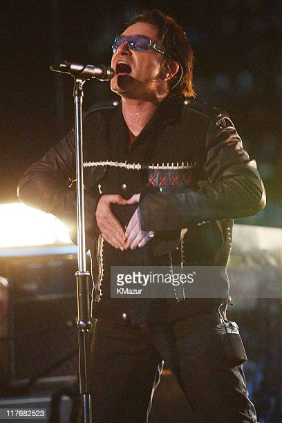 Bono lead singer of U2 uses his hands to outline a heart during the halftime show at Super Bowl XXXVI in the Superdome New Orleans Louisiana February...
