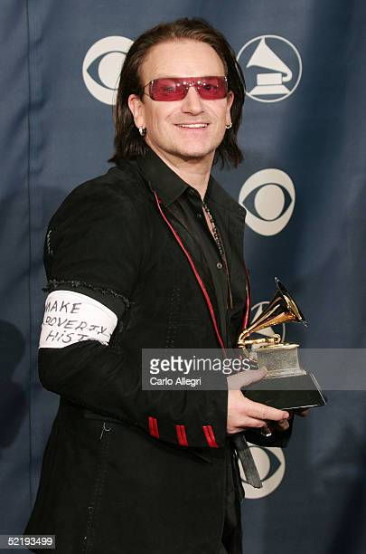 Bono of U2 holds their award for 'Best Rock Performance by a Group' backstage while wearing an arm band that reads 'Make Poverty History' during the...