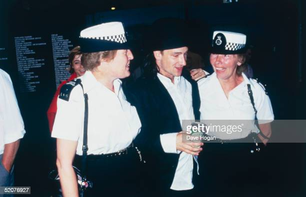 Bono of U2 makes friends with a couple of female police officers backstage at Wembley Stadium during the Live Aid Concert 13th July 1985