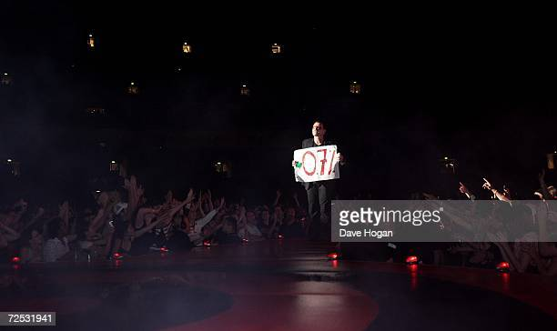 Bono of U2 performs on stage with a sign related to Make Poverty History at the first of three rescheduled Sydney dates on their Vertigo Tour at the...
