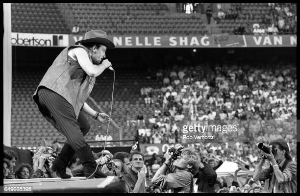 Bono of U2 performs to photographers at the front of the stage on The Joshua Tree Tour at Feyenoord Stadion De Kuip Rotterdam Netherlands 10th July...