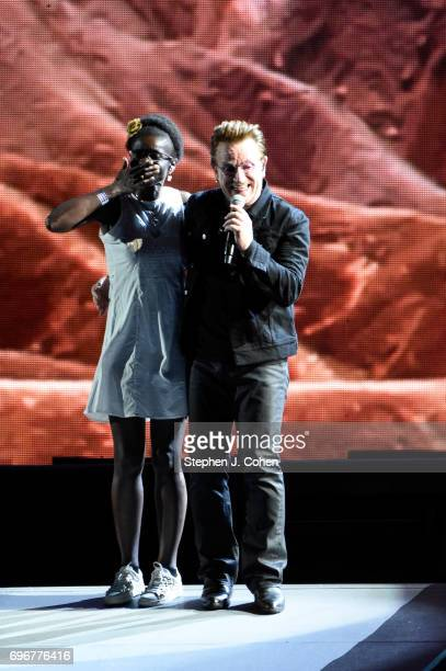 Bono of U2 performs with an unknown fan on stage at Papa John's Cardinal Stadium on June 16 2017 in Louisville Kentucky