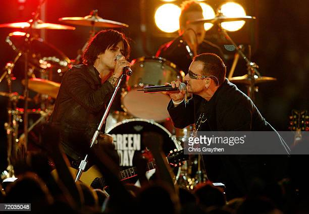 Bono of U2 performs with Billie Joe Armstrong the lead singer for the rock group Green Day prior to the Monday Night Football game between the...