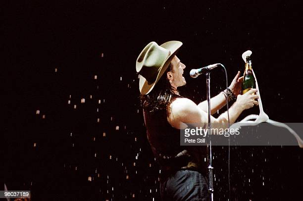 Bono of U2 sprays the crowd with champagne while performing on stage at Wembley Stadium on June 12th, 1987 on 'The Joshua Tree' tour in London,...
