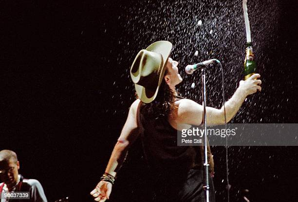 Bono of U2 sprays the crowd with champagne while performing on stage at Wembley Stadium on June 12th 1987 on 'The Joshua Tree' tour in London England