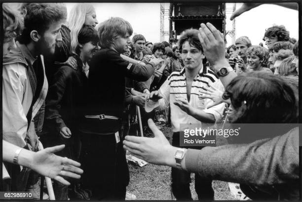 Bono of U2 walks amongst the front rows of the crowd while performing during the 'October' tour at Torhout festival, Belgium, 3rd July 1982.