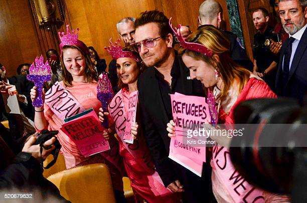 Bono poses with Cold Pink protestors during a State Foreign Operations and Related Programs Subcommittee hearing on causes and consequences of...