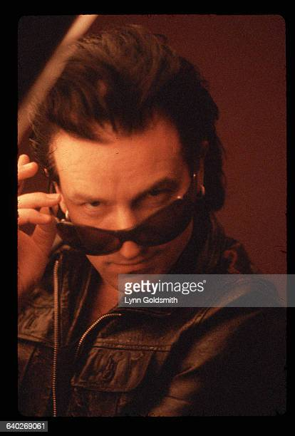 Bono singer for the rock group U2 pulls down his sunglasses to look at the camera