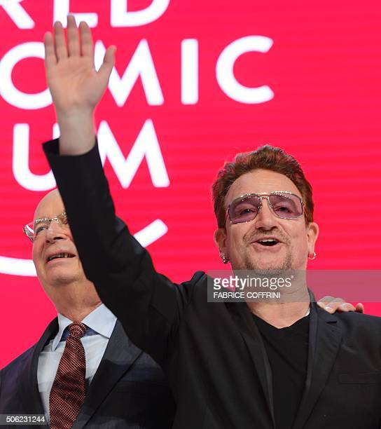 Bono singer of Irish band U2 and World Economic Forum founder and executive chairman Klaus Schwab wave during an event to celebrate the 10th...