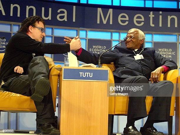 Bono singer of the Irish band U2 shakes hands with Archbishop Emeritus Desmond M Tutu of South Africa during the 'For Hope' session of the 32nd...