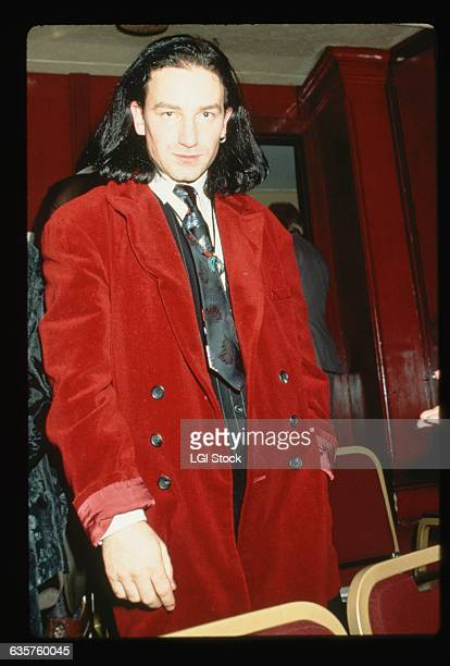 Bono singer of U2 wears a red velvet jacket at an event
