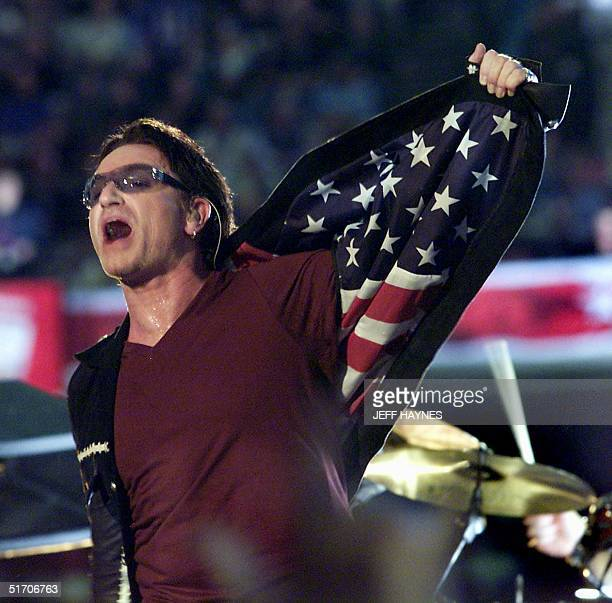 Bono singer with the Irish rock group U2 opens his jacket exposing an American flag as he performs during halftime 03 February 2002 of Super Bowl...
