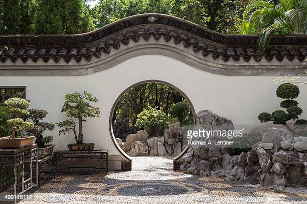 Bonsai trees and Chinese style round doorway at the Kowloon Walled City Park in Hong Kong, China, viewed from the front