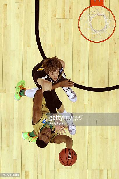 Bonzie Colson of the Notre Dame Fighting Irish drives to the basket against Ron Baker of the Wichita State Shockers during the Midwest Regional...