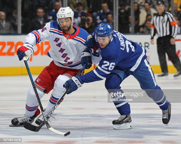 Boo Nieves of the New York Rangers skates for the puck against Par Lindholm of the Toronto Maple Leafs during an NHL game at Scotiabank Arena on...