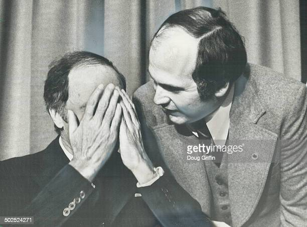 Prime Minister Pierre Trudeau covers his face in embarrassment as aide Ralph Coleman tells him he interrupted the playing of the Italian national...