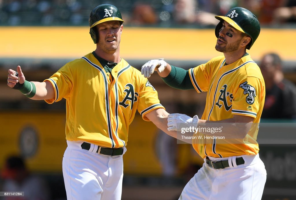 Boog Powell #3 (L) and Matt Joyce #23 (R) of the Oakland Athletics celebrates after Joyce hit a two-run homer against theBaltimore Orioles in the bottom of the seventh inning at Oakland Alameda Coliseum on August 13, 2017 in Oakland, California. The Athletics won the game 9-3.