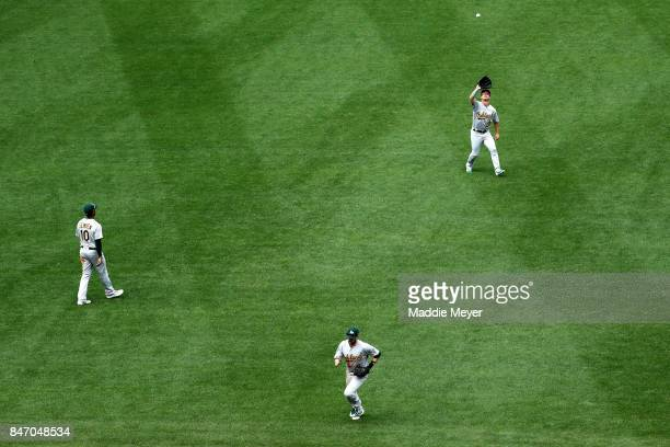 Boog Powell of the Oakland Athletics catches a fly ball hit by Mookie Betts of the Boston Red Sox during the seventh inning at Fenway Park on...
