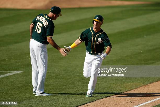 Boog Powell of the Oakland Athletics celebrates with third base coach Steve Scarsone after hitting a tworun home run in the eighth inning against the...