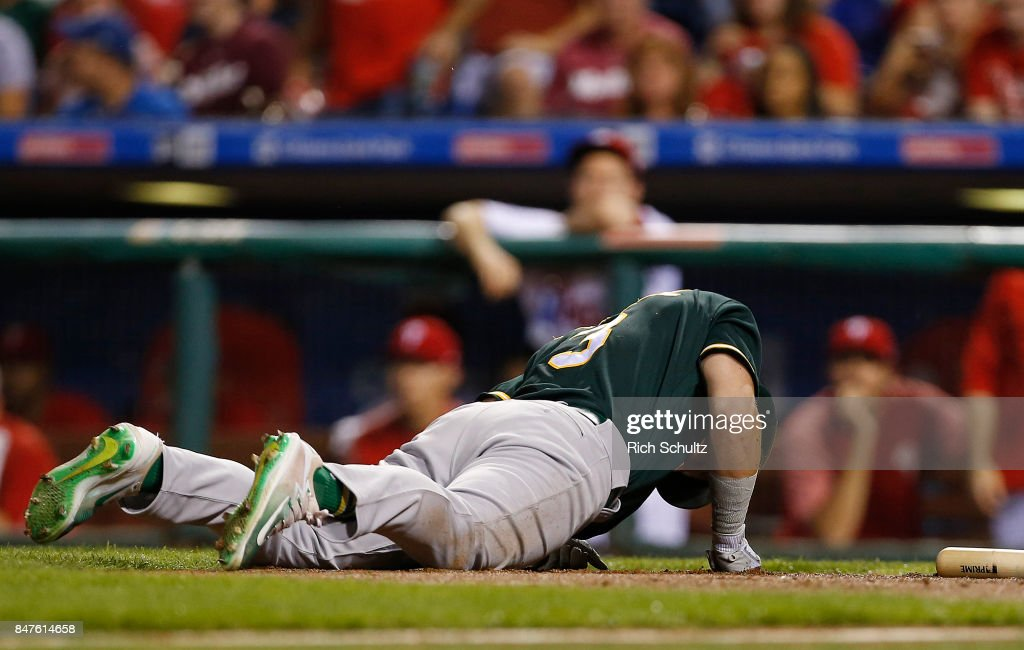 Boog Powell #3 of the Oakland Athletics hits the ground after getting hit by a foul ball off his bat against the Philadelphia Phillies during the second inning of a game at Citizens Bank Park on September 15, 2017 in Philadelphia, Pennsylvania. The A's defeated the Phillies 4-0.
