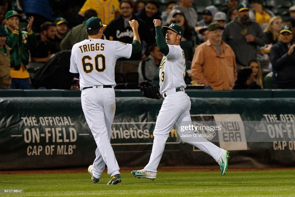 Boog Powell #3 of the Oakland Athletics is congratulated by Andrew Triggs #60 after catching a fly ball off the bat of Ryan Rua (not pictured) of the Texas Rangers during the fourth inning at the Oakland Coliseum on April 2, 2018 in Oakland, California. The Oakland Athletics defeated the Texas Rangers 3-1.