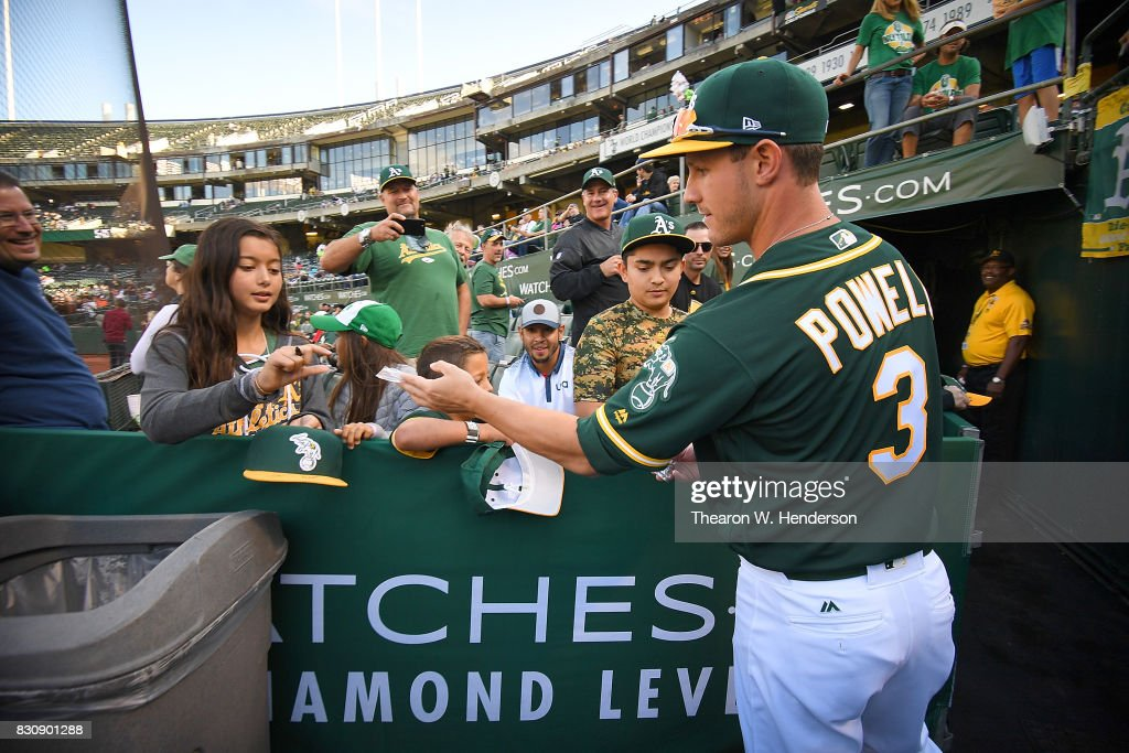 Boog Powell #3 of the Oakland Athletics passes out Topps trading cards to fans prior to the start of their game against the Baltimore Orioles at Oakland Alameda Coliseum on August 12, 2017 in Oakland, California.