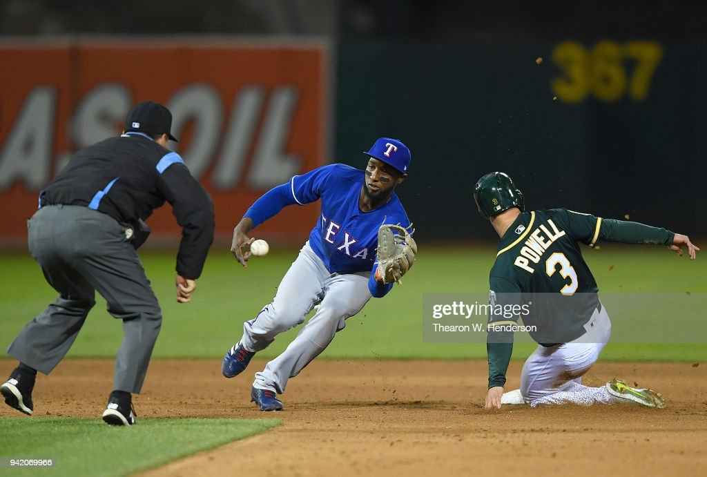 Boog Powell #3 of the Oakland Athletics steals second base beating the throw down to Jurickson Profar #19 of the Texas Rangers in the bottom of the eighth inning at the Oakland Alameda Coliseum on April 4, 2018 in Oakland, California.