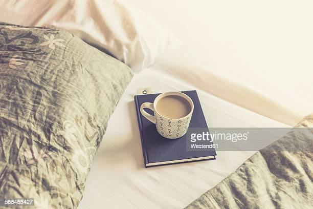 Book and cup of white coffee on a bed