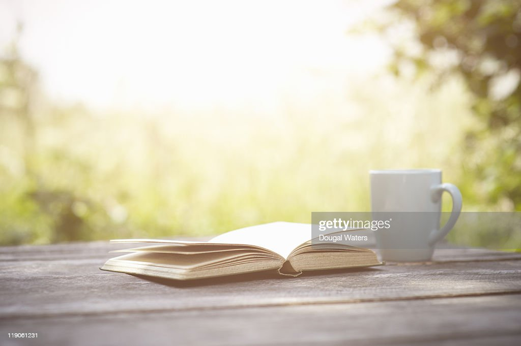 Book and cup on garden table. : Stock Photo