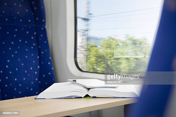 Book and digital tablet in a train