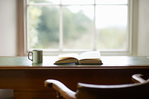 Book and mug on traditional writing desk beside window. - gettyimageskorea