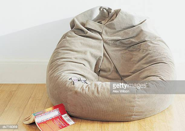 A Book and Spectacles Lying by a Beanbag