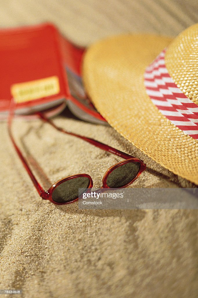 Book and sunglasses with hat on sand : Stockfoto