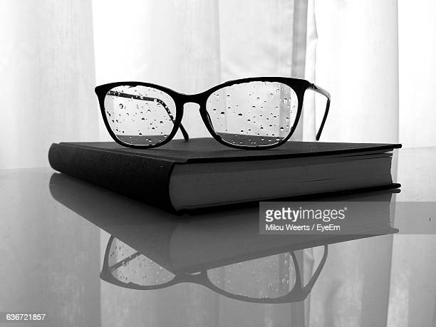 Book And Wet Eyeglass On Table At Home