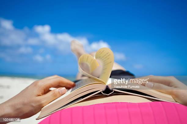 Book making a heart shape on beach.