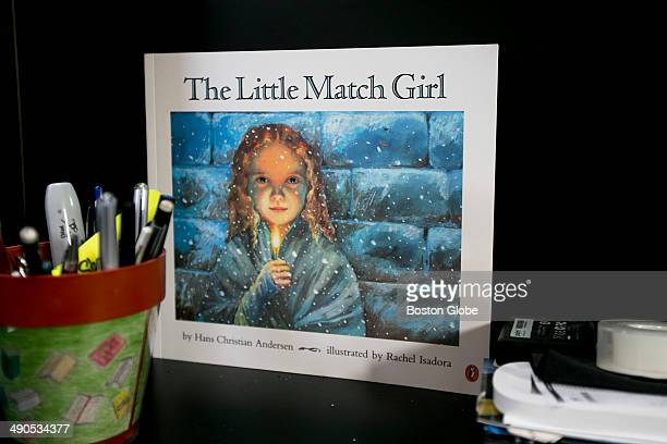 A book named The Little Match Girl by Hans Christian Andersen was photographed at Rebecca Goldstein's desk She keeps the book there because the girl...