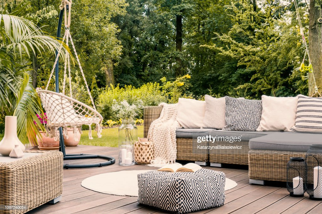 Book on a black and white pouf in the middle of a bright terrace with a rattan corner sofa, hanging chair and round rug. Real photo : Stock Photo