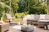 Book on a black and white pouf in the middle of a bright terrace with a rattan corner sofa, hanging chair and round rug. Real photo