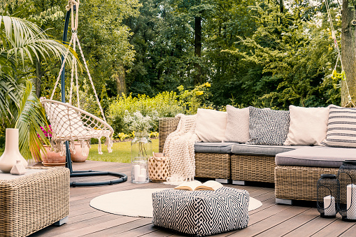 Book on a black and white pouf in the middle of a bright terrace with a rattan corner sofa, hanging chair and round rug. Real photo 1007240024