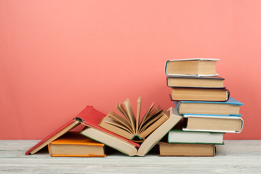 Book stacking. Open book, hardback books on wooden table and pink background. Back to school. Copy space for text 938171020