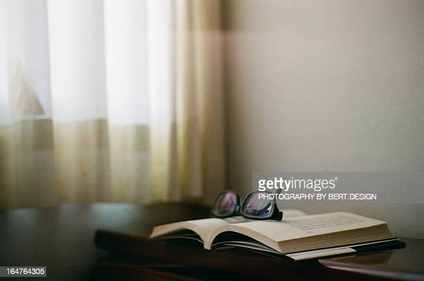 Book with glasses and window curtain.