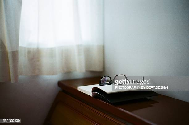 Book with glasses and window curtain