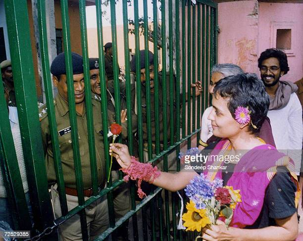 Booker Award winning author and activist Arundhati Roy presents a flower to the jail guards as she leaves the Tihar Central Jail after serving a...