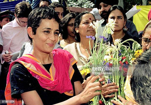 Booker Prizewinning author Arundhati Roy smiles as she receives flowers from supporters 07 March 2002 upon her release from jail in New Delhi Roy was...