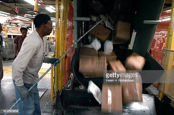 Booker Sowell <cq> a mail handler pulls large boxes and packages out of bins that then go onto a conveyor belt to be processed at the facility This...